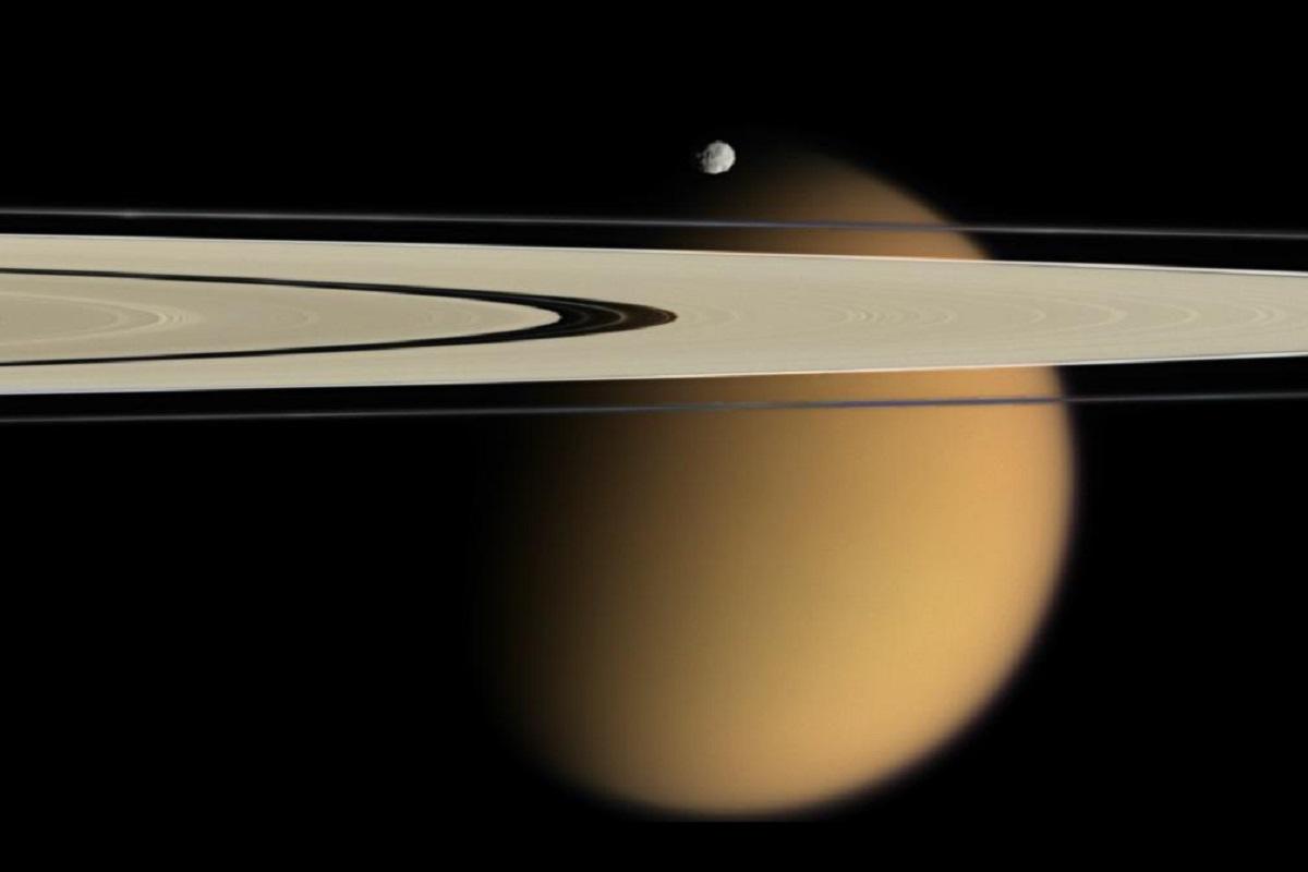 Титан на фоне колец Сатурна (Снимок автоматической межпланетной станции Cassini–Huygens)